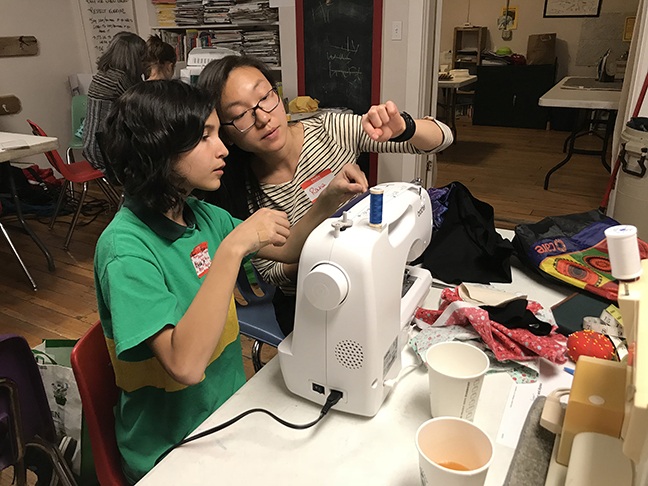 Honors students Rana sitting at a sewing machine helping a student.