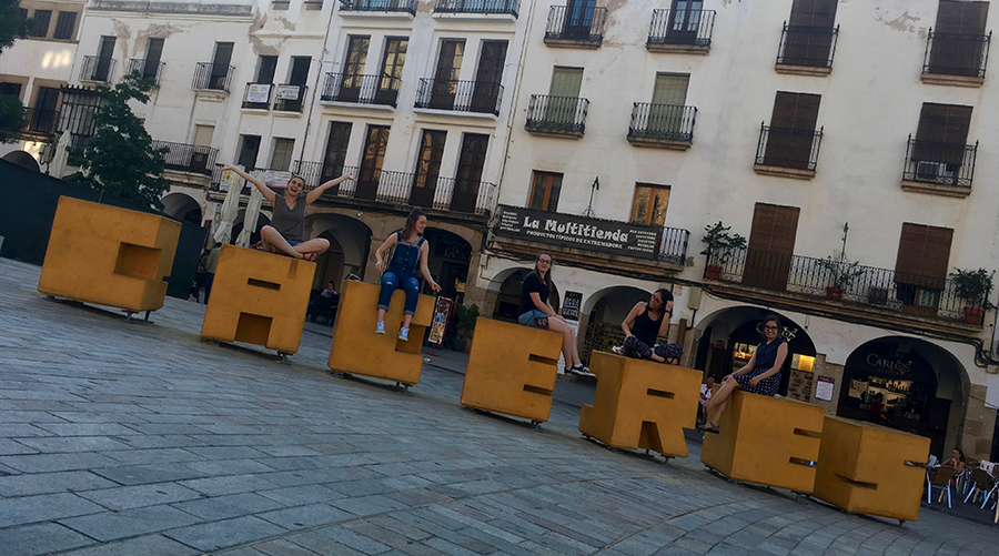 Students sitting on top of very large wood carved yellow block letters spelling Caceres